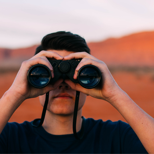 Man looking through binoculars. Dealing with trauma is hard, especially when you don't know what is trauma and the common effects of trauma. Ready to make that change? Learn more from a trauma therapist.